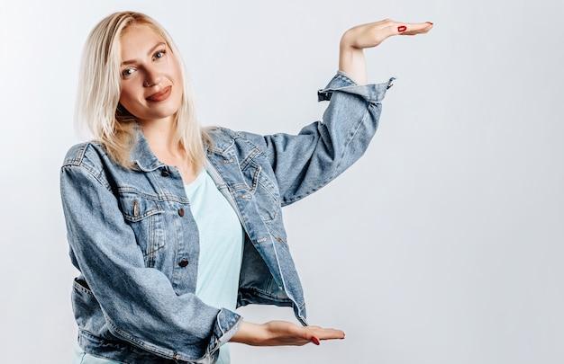 Sorridente ragazza bionda mostra grandi dimensioni con le mani su sfondo grigio isolato