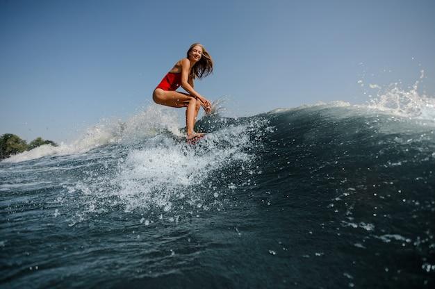 Ragazza bionda sorridente che sta sul wakeboard rosso sul lago