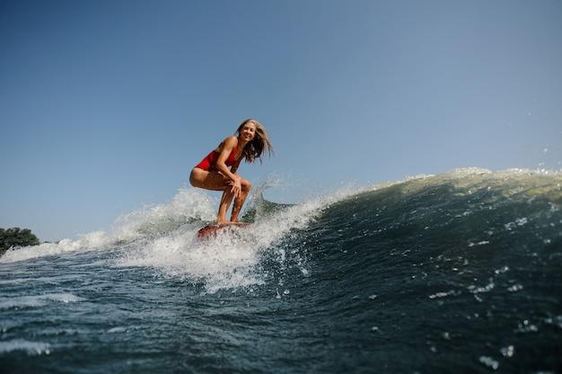 Ragazza bionda sorridente che sta sul wakeboard sul lago