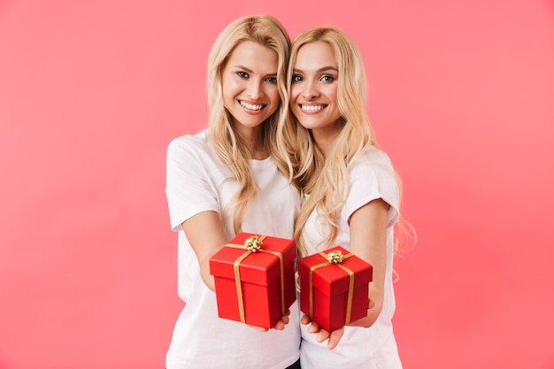 Gemelli biondi sorridenti che indossano in magliette che danno i contenitori di regalo alla macchina fotografica sopra la parete rosa