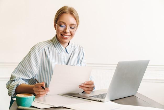 Architetto sorridente della donna bionda in occhiali che lavora con il computer portatile mentre progetta il progetto sul posto di lavoro