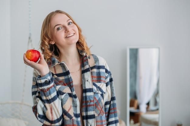 Donna bionda sorridente che tiene mela rossa e che guarda l'obbiettivo su sfondo domestico. mangiare sano, concetto di veganismo