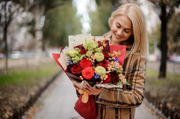 Donna bionda sorridente che esamina bello mazzo nel parco di autunno