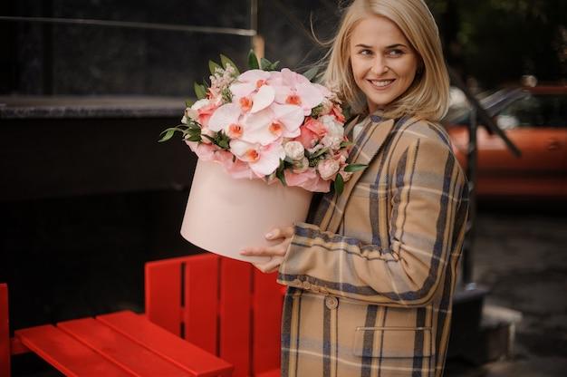 Donna bionda sorridente in cappotto autunno plaid con una scatola di fiori rosa