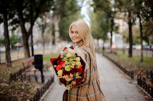 Donna bionda sorridente in cappotto scozzese che tiene un mazzo luminoso di fiori che cammina sul vicolo