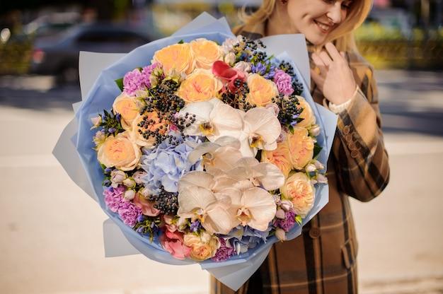 Donna bionda sorridente in cappotto a quadri che tiene un grande mazzo adorabile di fiori