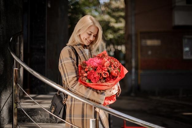 Donna bionda sorridente in cappotto a quadri con un grande mazzo di fiori rosso