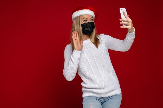 Sorridente donna bionda in santa cappello e maschera protettiva nera sventolando qualcuno che chiama tramite telefono cellulare durante la pandemia. isolare sul rosso. copia spazio.