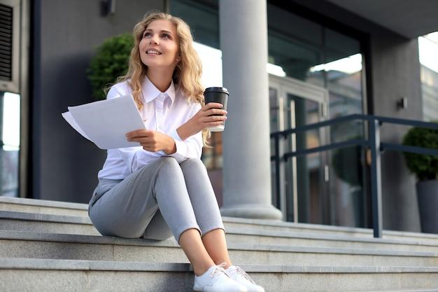 Donna bionda sorridente in camicia seduta all'aperto e distoglie lo sguardo mentre tiene in mano documenti e tazza di caffè.