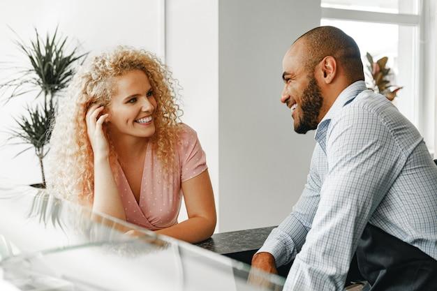 Donna bionda sorridente che parla con un cameriere di una caffetteria al bancone