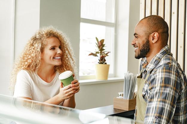 Donna bionda sorridente che parla con un cameriere di una caffetteria