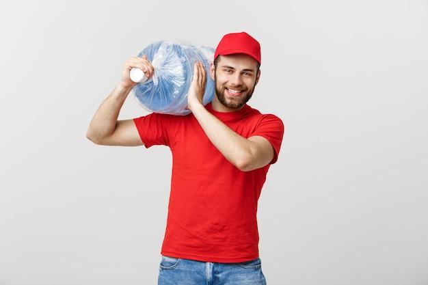 Sorridente corriere di consegna di acqua in bottiglia in t-shirt rossa e serbatoio di trasporto tappo