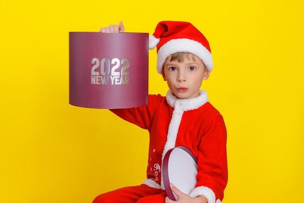 Ragazzo sorridente vestito da babbo natale con in mano una scatola regalo rossa rotonda con la scritta capodanno 2022