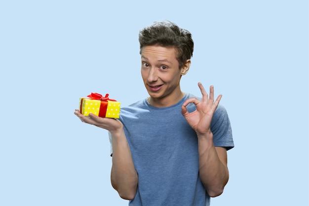 Ragazzo sorridente che tiene una confezione regalo e mostra un gesto ok