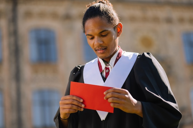 Ragazzo sorridente che tiene fogli di carta rossi con i suoi appunti offrendo un discorso durante la laurea