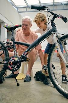 Ragazzo sorridente che abbraccia il nonno che ripara la bicicletta