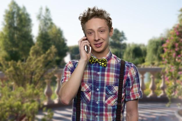 Il ragazzo sorridente sta parlando al telefono. il ragazzo ben vestito ha una conversazione. la natura dell'estate beautifyul sullo sfondo.