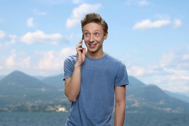 Il ragazzo sorridente sta parlando al telefono. giovane ragazzo positivo in maglietta. montagne sullo sfondo.