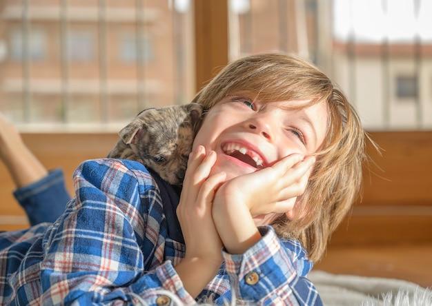 Il ragazzo sorridente gioca con il cagnolino che gli si arrampica sulla schiena