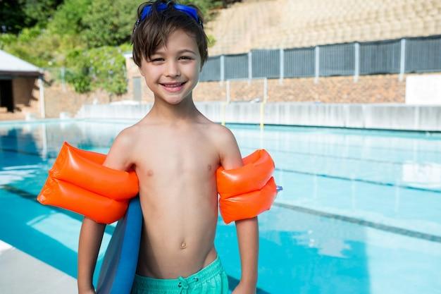 Ragazzo sorridente in piedi con kickboard e fascia da braccio a bordo piscina