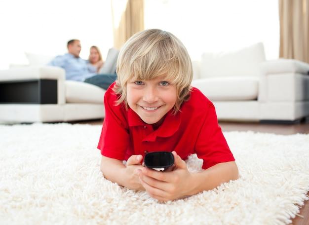 Ragazzo sorridente che guarda tv che si trova sul pavimento