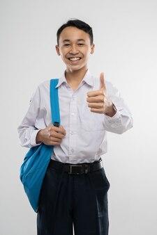 Un ragazzo sorridente che indossa un'uniforme scolastica e porta uno zaino con i pollici in su