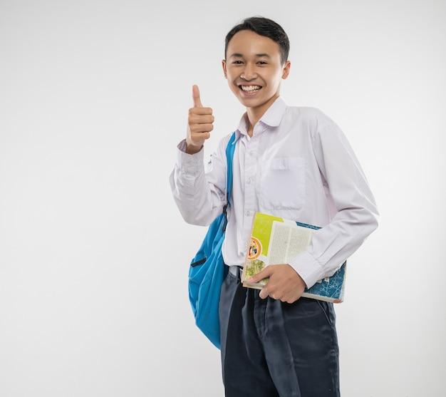 Un ragazzo sorridente indossa un'uniforme scolastica e porta uno zaino e un libro con i pollici in su per la telecamera