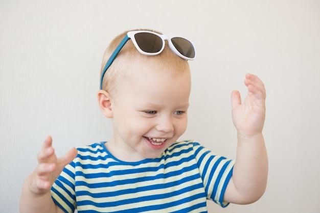 Ragazzo sorridente con gli occhi azzurri a strisce ritratto della maglietta