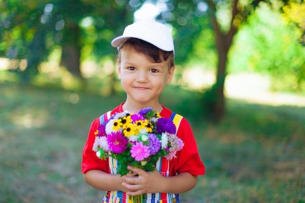 Ragazzo sorridente con un mazzo di fiori di campo una sorpresa per la mamma in vacanza un bambino con i fiori in...