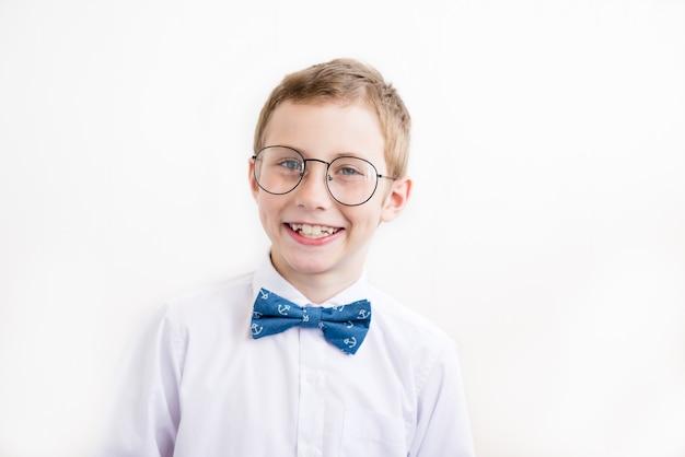 Ragazzo sorridente con gli occhiali in camicia bianca con farfalla su uno sfondo bianco