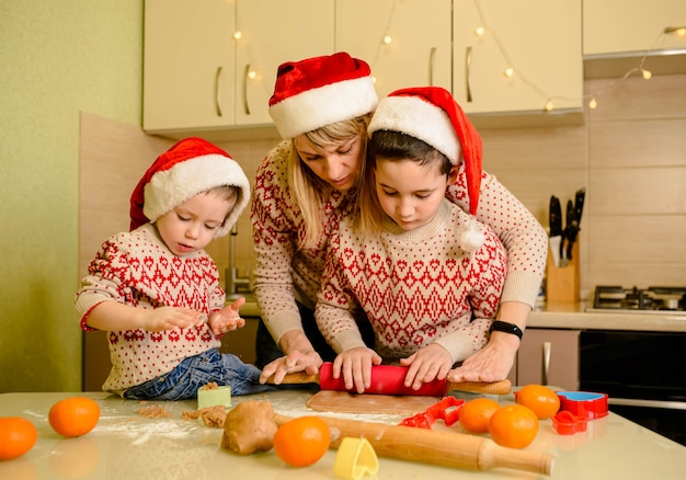 Ragazzi sorridenti e madre che cucinano i biscotti di natale a casa cucinando