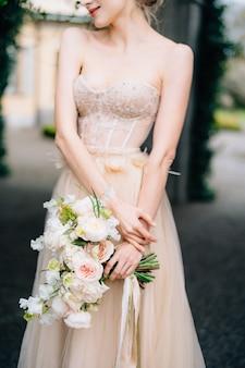 Sposa sorridente in un bel vestito con le spalle nude che tiene un mazzo di fiori rosa