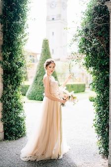 Sposa sorridente in un vestito con un mazzo di fiori contro i vecchi edifici