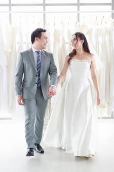 La sposa e lo sposo sorridenti si guardano, tenendosi per mano nel camerino del negozio di matrimoni. uomo asiatico e donna felici il giorno del matrimonio imminente. giorno migliore di concetto.