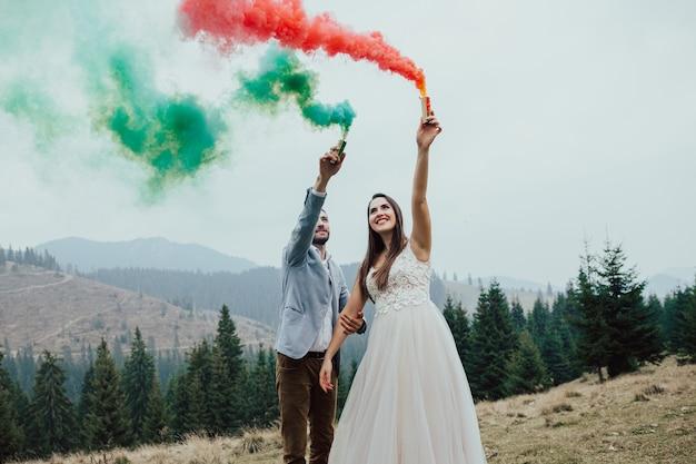 La sposa e lo sposo sorridenti con fumo colorato sulla superficie del paesaggio montano.