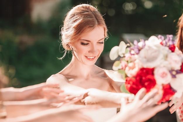 Sorridente sposa consegna bouquet di nozze ai suoi amici