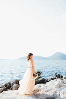 Sorridente sposa in un abito da sposa pastello sorge su una roccia a picco sul mare con un mazzo di fiori