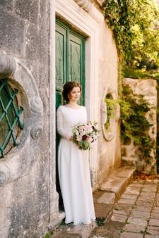 La sposa sorridente sta sullo sfondo di un edificio con un bellissimo mazzo di fiori