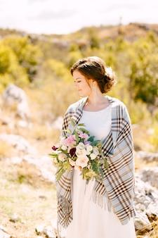 Sposa sorridente con uno scialle a scacchi sulle spalle e un bellissimo mazzo di fiori