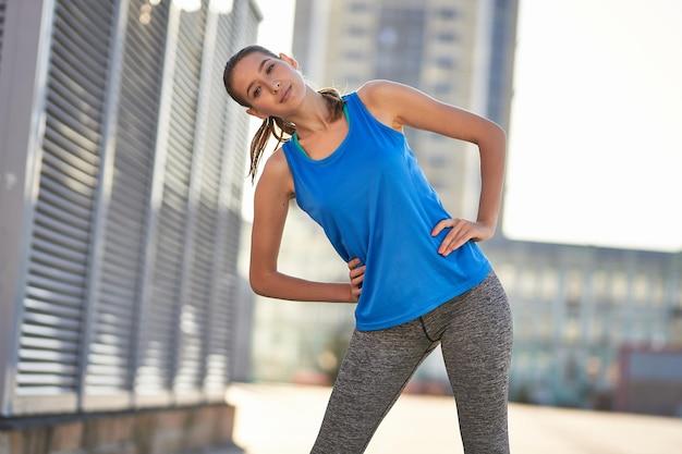 Bruna sorridente in una maglietta sportiva blu all'aperto