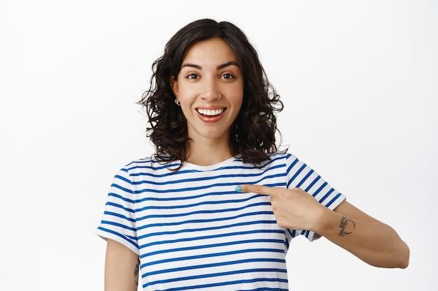 Sorridente ragazza bruna che indica se stessa con la faccia felice, autopromozione, parla di risultati personali, volontariato, in piedi su bianco