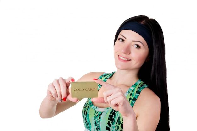 Ragazza sorridente del brunette con capelli lunghi che mostrano la carta di credito dell'oro.