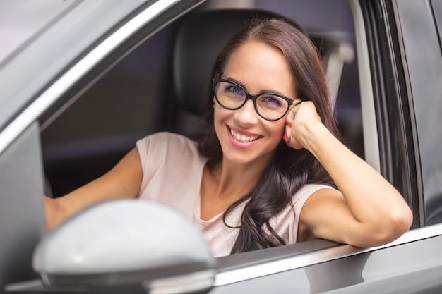 Bruna sorridente con gli occhiali guida un'auto, con un braccio fuori dal finestrino aperto sul lato della sua auto.
