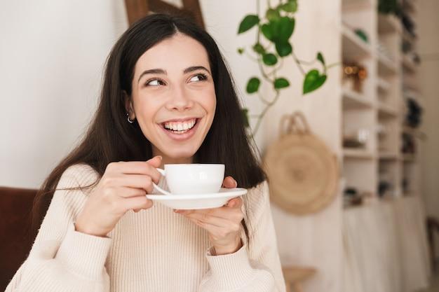 Sorridente donna bruna tenendo la tazza e bere il caffè mentre si fa colazione in cucina a casa