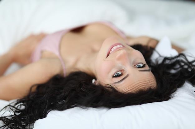 La donna sorridente del brunette si trova sul letto bianco