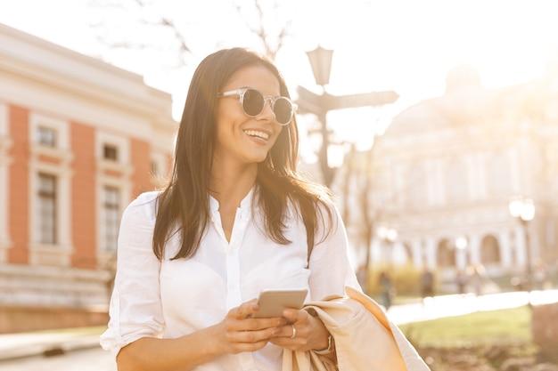 Donna castana sorridente in camicia e occhiali da sole che tengono smartphone