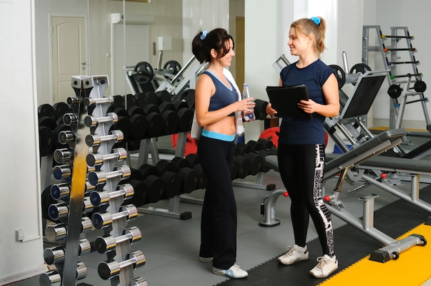 Sorridente donna bruna con asciugamano e bottiglia d'acqua in mano si consulta con istruttore di fitness in palestra