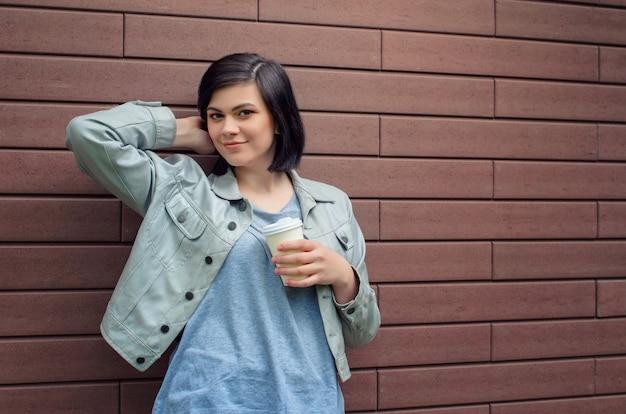 Sorridente ragazza brunnete con tunnel nelle orecchie in una giacca di pelle beige con una tazza di caffè in piedi davanti al muro di mattoni.
