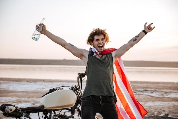 Uomo brutale sorridente in mantello della bandiera americana seduto sulla sua moto con le mani in alto