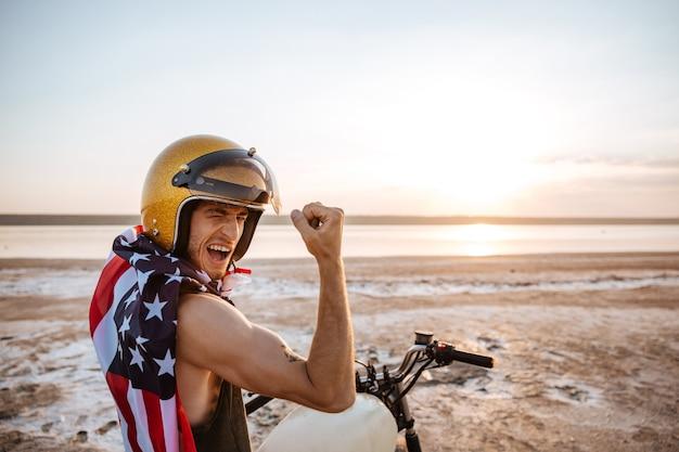 Uomo brutale sorridente in casco dorato e mantello con bandiera americana seduto sulla sua moto che mostra bicipiti all'aperto